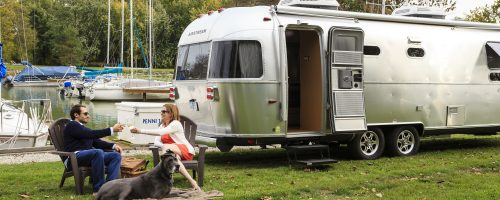 Airstream camper and couple with a dog by the lake